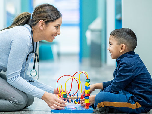 Nurse and child patient smiling at each other while playing