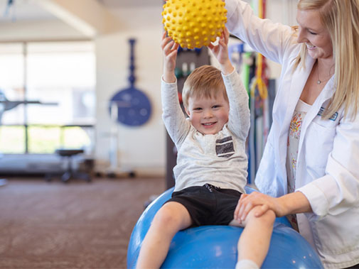 Child lifting a ball as a part of physical therapy with a physicial therapist